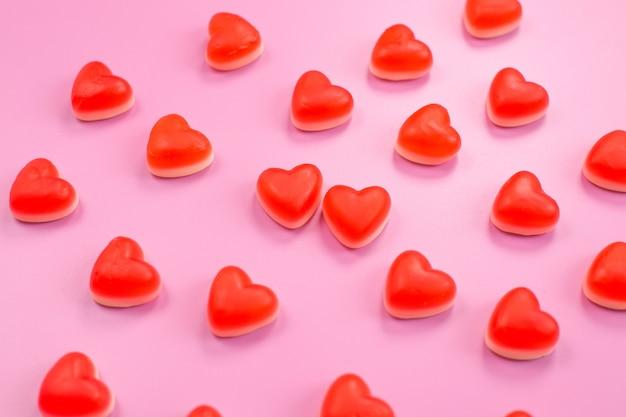 Viele rote leckere herzförmige gummibonbons.