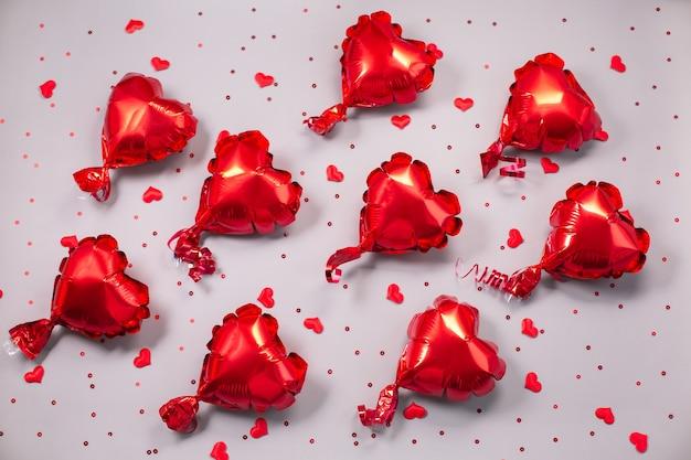 Viele rote luftballons aus herzförmiger folie. liebeskonzept. valentinstag