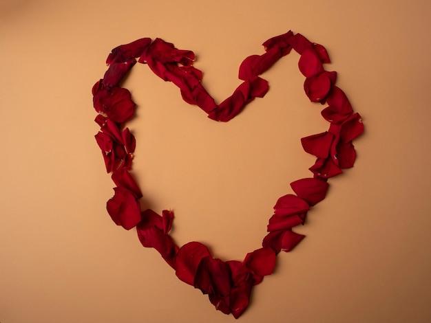 Viele rote rosenblätter liegen in form eines großen roten herzens auf einem orangefarbenen hintergrund