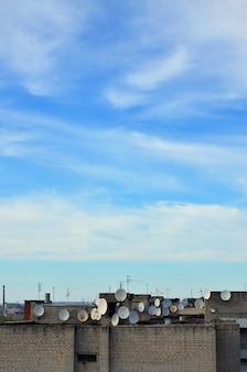 Viele satellitenfernsehantennen auf der dachspitze unter einem blauen himmel