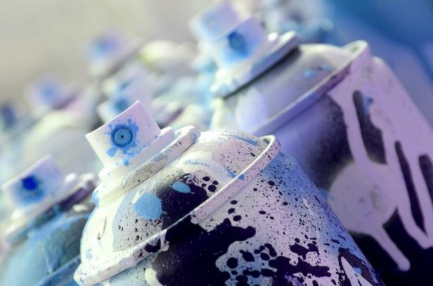 Viele schmutzige und gebrauchte sprühdosen mit hellblauer farbe.