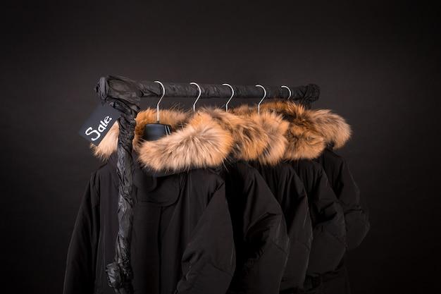 Viele schwarze mäntel, jacke mit fell an der kapuze, die am kleiderständer hängt.