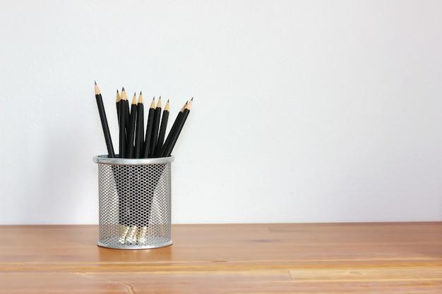 Viele schwarzen bleistifte im korb auf hölzernem schreibtisch oder tabelle mit weißer wand, kopienraum.
