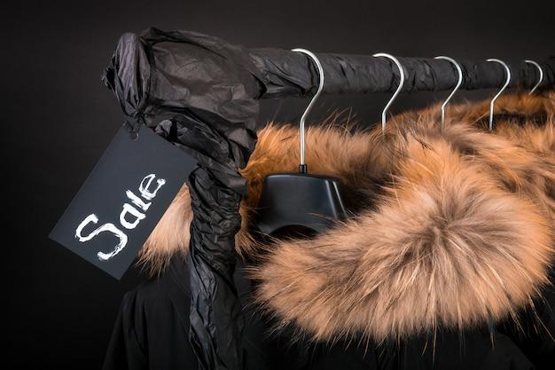 Viele schwarzen mäntel, jacke mit fell an der kapuze, die am kleiderständer hängt.