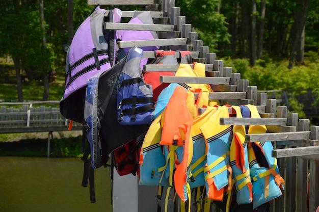Viele schwimmwesten hängen an einem holzständer am wasser