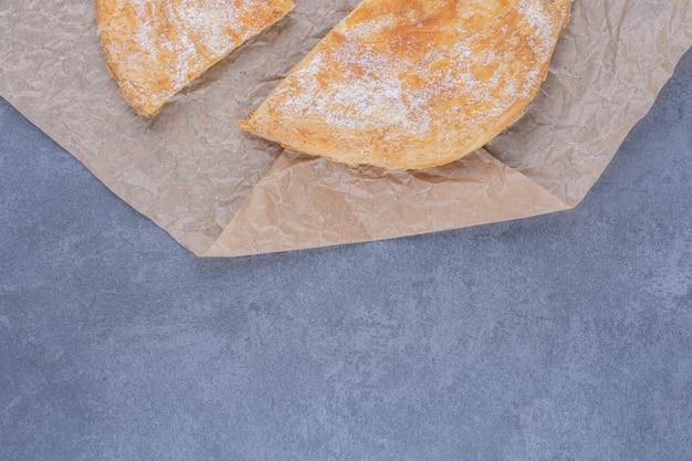 Viele stücke leckeren kuchens mit zuckerpulver auf einem dauerhaften papier