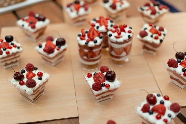 Viele süße desserts in tassen mit sommerbeeren.