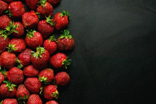 Viele süße erdbeeren liegen auf einem schwarzen hintergrund