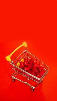 Viele süße herzförmige bonbons im supermarktwagen auf rotem papierhintergrund