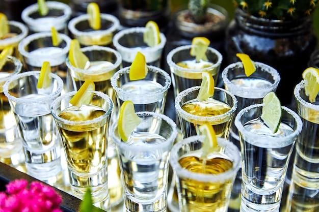 Viele tequila-gläser mit zitrone und kaktus