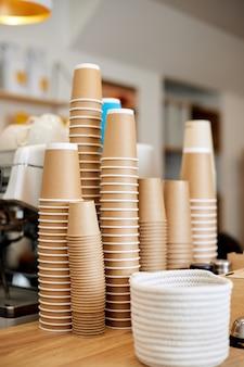 Viele trinkende einweg-pappbecher in haufen. stapel pappbecher im café