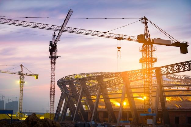 Viele turmdrehkrane bauen nachts große wohngebäude.