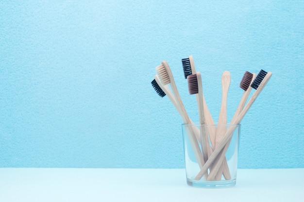 Viele umweltfreundlichen bambuszahnbürsten in einem glas auf einem blauen hintergrund mit einem kopienraum, konzept null abfall
