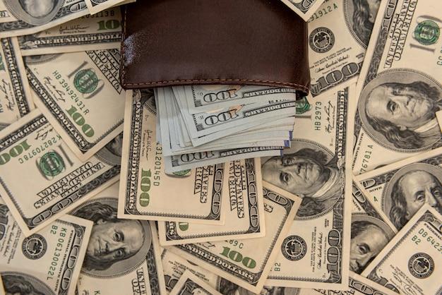 Viele us-dollar in der nähe der brieftasche des menschen, spart konzept