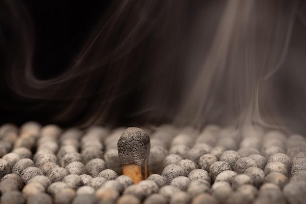 Viele verbrannte streichhölzer mit einem großen in der mitte, der sich von den anderen abhebt