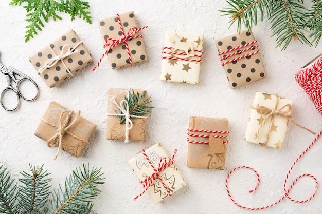 Viele verpackte weihnachtsgeschenkboxen und fichte auf weißem tisch.