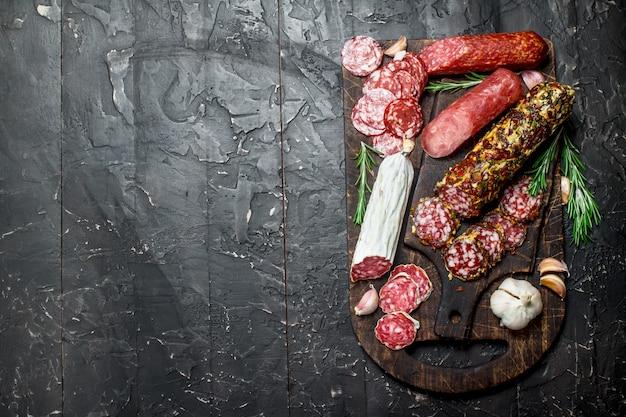 Viele verschiedene arten von salami auf holzbrett. auf schwarzem rustikalem tisch.