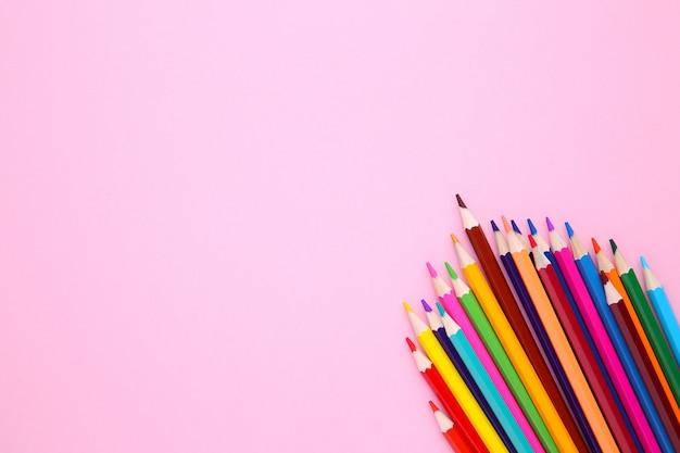 Viele verschiedene buntstifte auf rosa
