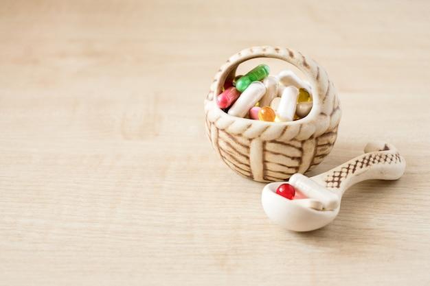 Viele verschiedene farbige pillen und kapseln in keramikvase