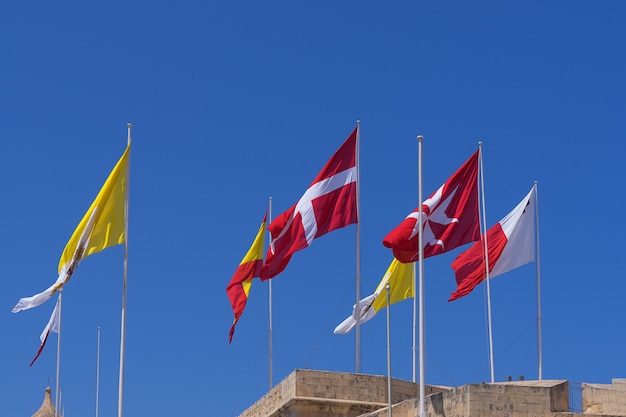 Viele verschiedene flaggen über der stadt birgu