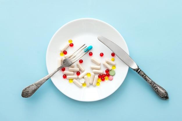 Viele verschiedene gewichtsverlustpillen und ergänzungen als lebensmittel auf runder platte