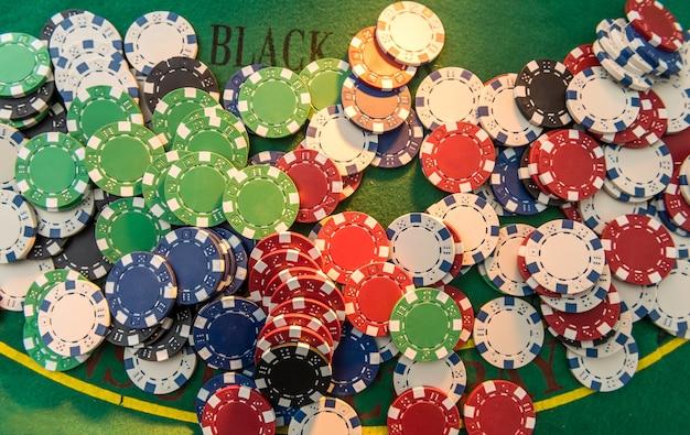 Viele verschiedene kosten-pokerchips auf dem spieltisch. großer spieleinsatz auf dem grünen tuchfeld, nahaufnahme