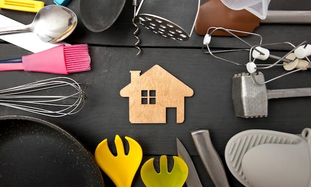 Viele verschiedene küchenutensilien auf dem holztisch und ein kleines holzhaus dazwischen