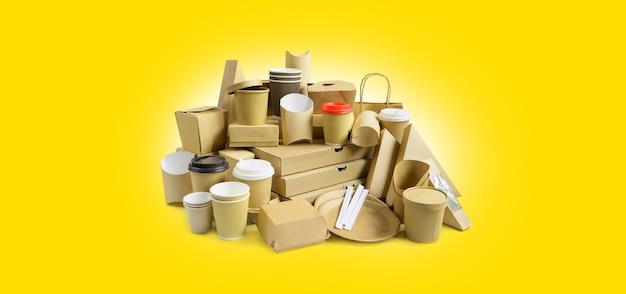 Viele verschiedene lebensmittelbehälter zum mitnehmen, pizzakarton, kaffeetassen im halter und papierschachteln auf gelbem hintergrund.