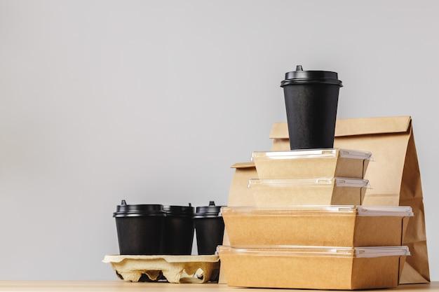 Viele verschiedene lebensmittelbehälter zum mitnehmen, pizzaschachtel, kaffeetassen und papiertüten auf hellgrauem hintergrund. lebensmittellieferservice