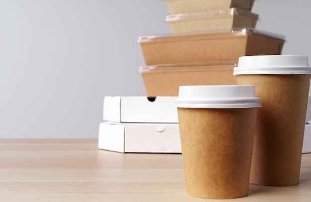 Viele verschiedene lebensmittelbehälter zum mitnehmen, pizzaschachtel, kaffeetassen und papiertüten auf hellgrauem hintergrund