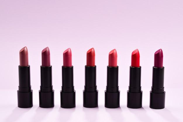 Viele verschiedene lippenstifte, verschiedene farben auf lila hintergrund. platz für text oder design.
