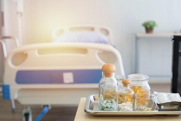 Viele verschiedene medikamente, pillen und andere medikamente auf dem holztisch mit medizinischen geräten im hintergrund.