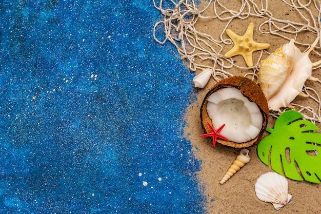 Viele verschiedene muscheln, sternfische, kokosnussseile und blaues glitzern wie meer