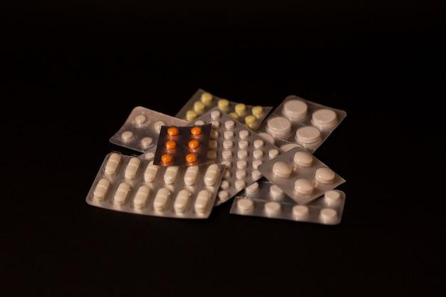 Viele verschiedene packungen mit pillen, medikamenten, beruhigungsmitteln, virostatika, vitaminen auf schwarzem hintergrund