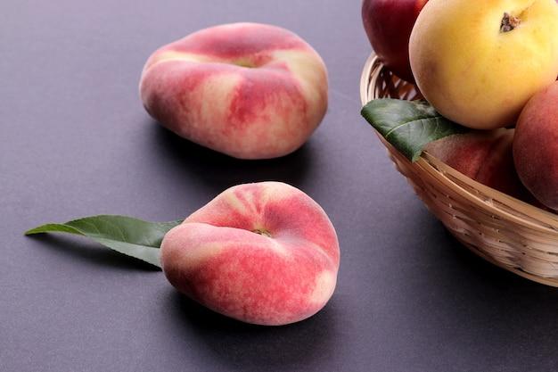 Viele verschiedene pfirsichsorten im weidenkorb