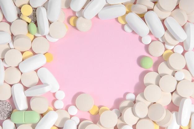 Viele verschiedene pillen auf einem rosa hintergrund mit platz für text