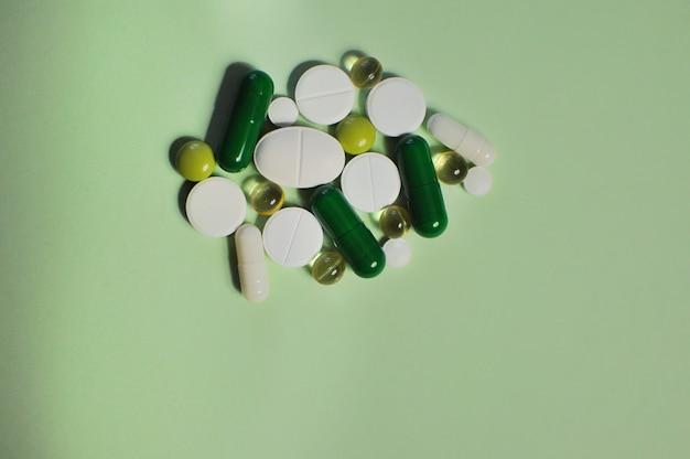 Viele verschiedene pillen auf grünem tisch viele bunte verschiedene pillen, einschließlich antiviraler medikamente