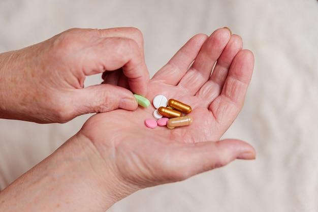Viele verschiedene pillen in der hand einer älteren person. alter mann nimmt eine pille von seiner handfläche.