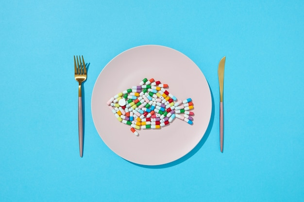 Viele verschiedene pillen und nahrungsergänzungsmittel als lebensmittel auf rundem weißen teller mit gabel und messer. diätpillen und nahrungsergänzungsmittel für das diätkonzept. draufsicht.