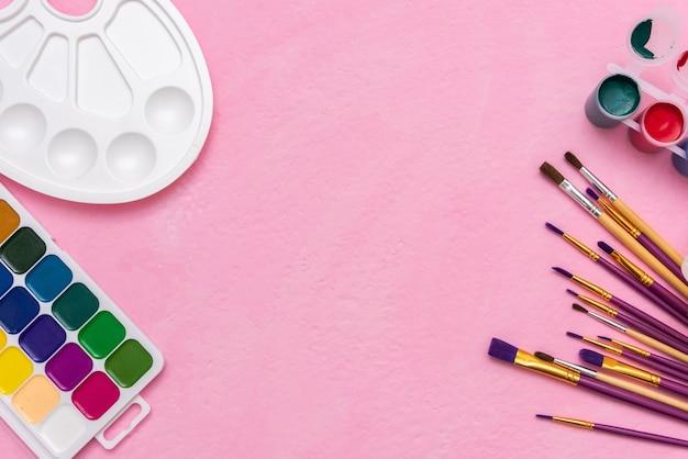 Viele verschiedene pinsel zum zeichnen mit gouache und palette auf rosa, flachem lay