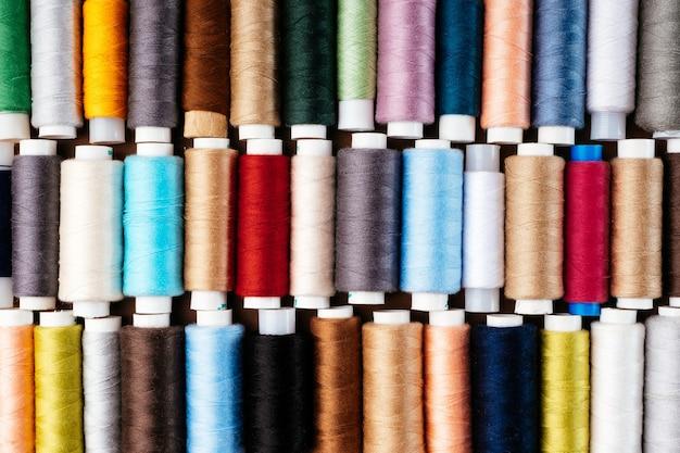 Viele verschiedene rollen mit fäden, flachgelegt, draufsicht. farbige fäden, nahaufnahme, heller hintergrund.