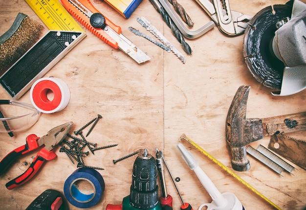 Viele verschiedene werkzeuge auf dem schmutzigen holztisch