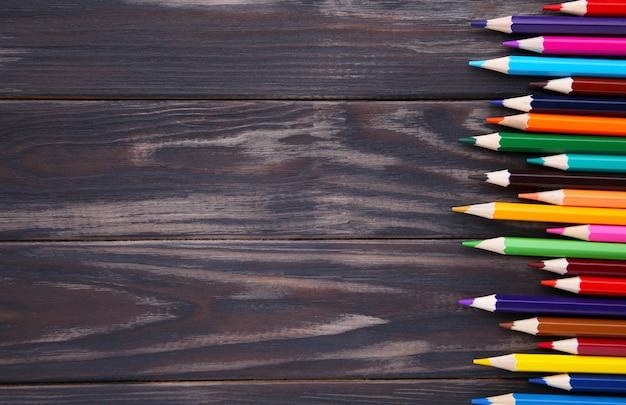 Viele verschiedenen buntstifte auf braunem holz