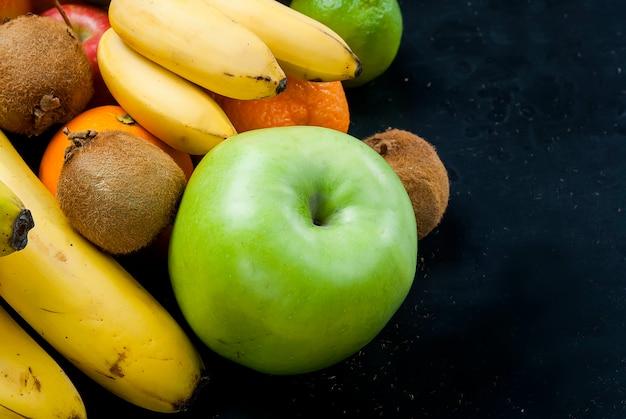 Viele verschiedenen früchte auf einem schwarzen hintergrund