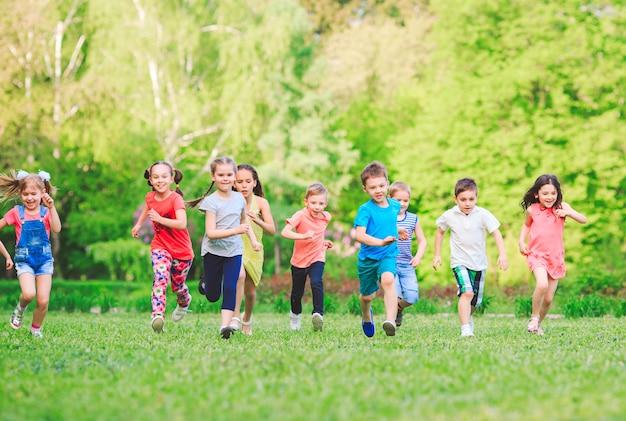 Viele verschiedenen kinder, jungen und mädchen, die in den park am sonnigen sommertag in der zufälligen kleidung laufen