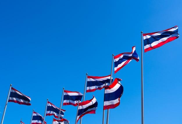 Viele von thailand flagge, die oben auf fahnenmast gegen blauen himmel weht