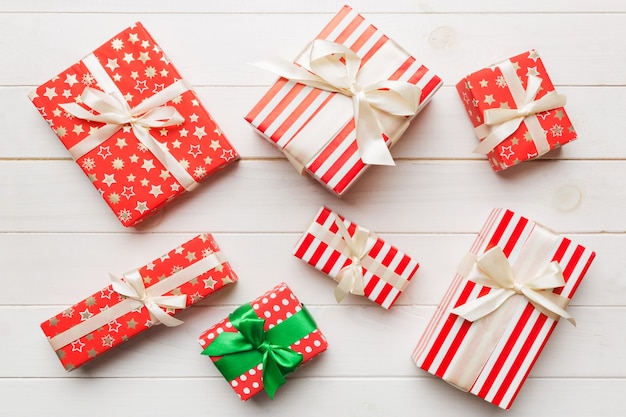 Viele weihnachtsgeschenkboxen in farbigem papier auf dem tisch dekoriert, draufsicht aus nächster nähe. viele präsentieren neujahrsgeschenk