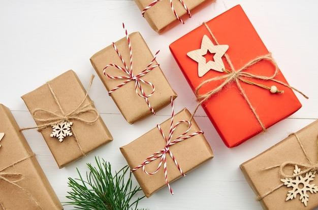 Viele weihnachtsgeschenkboxen mit kiefernzweigen auf weiß