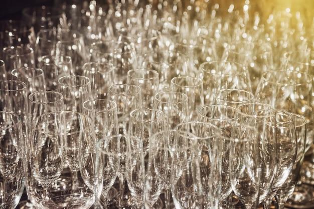 Viele weingläser in reihe für hintergründe. leere saubere gläser, die in reihe auf der küche stehen, die vom barkeeper für die champagner-event-zeremonie zubereitet wird. mehrere aus transparentem glas auf gestell. platz für website kopieren