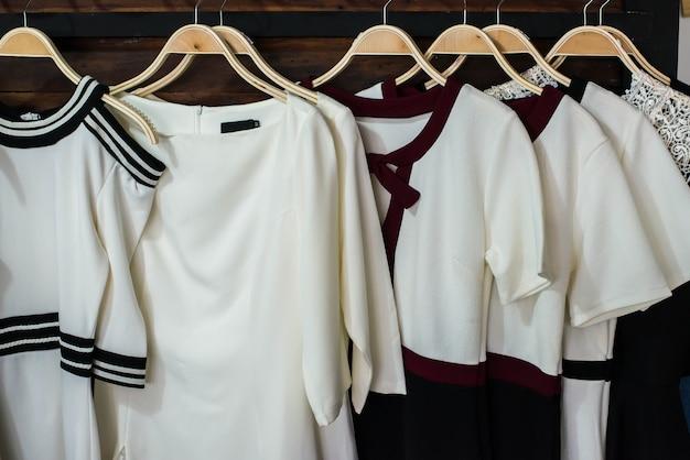 Viele weiße blusen auf kleiderbügeln in der umkleidekabine.
